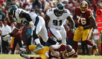 Washington Redskins quarterback Kirk Cousins, bottom, fumbles in front of Philadelphia Eagles defensive tackle Fletcher Cox (91), defensive end Brandon Graham, left, and Redskins offensive tackle Morgan Moses (76) in the second half of an NFL football game, Sunday, Sept. 10, 2017, in Landover, Md. Cox recovered the fumble and scored a touchdown on the play. Philadelphia won 30-17. (AP Photo/Alex Brandon)