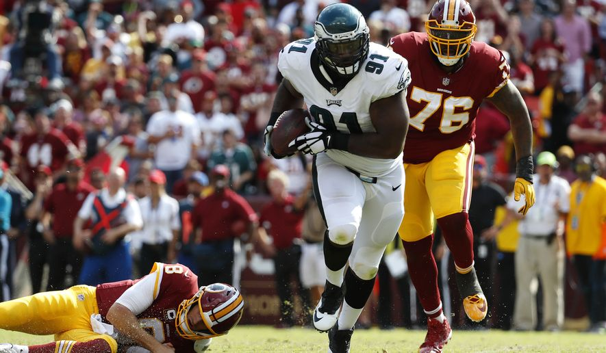 Philadelphia Eagles defensive tackle Fletcher Cox, center, rushes for a touchdown in front of Washington Redskins offensive tackle Morgan Moses (76) after recovering a fumble by Redskins quarterback Kirk Cousins, bottom left, in the second half of an NFL football game, Sunday, Sept. 10, 2017, in Landover, Md. Philadelphia won 30-17. (AP Photo/Alex Brandon)
