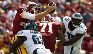 Washington Redskins quarterback Kirk Cousins, left, is sacked by Philadelphia Eagles defensive tackle Timmy Jernigan in the second half of an NFL football game, Sunday, Sept. 10, 2017, in Landover, Md. (AP Photo/Alex Brandon)
