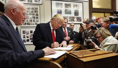 New Hampshire Secretary of State Bill Gardner watched Donald Trump fill out his papers to be on the nation's earliest presidential primary ballot in 2015. Mr. Gardner says he will remain on the Presidential Advisory Commission on Election Integrity, though he disagrees with voter fraud allegations made by the panel's vice chairman about his state. (Associated Press/File)