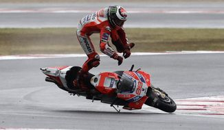 Moto GP rider Jorge Lorenzo of Spain falls off his bike during the San Marino Motorcycle Grand Prix at the Misano circuit in Misano Adriatico, Italy, Sunday, Sept. 10, 2017. (AP Photo/Antonio Calanni)