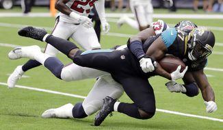 Jacksonville Jaguars running back Leonard Fournette (27) is hit by Houston Texans defensive end Joel Heath (93) during the first half of an NFL football game Sunday, Sept. 10, 2017, in Houston. (AP Photo/David J. Phillip)