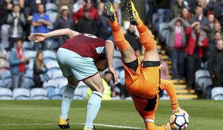 Burnley goalkeeper Tom Heaton catches the ball before landing awkwardly on his shoulder during the English Premier League soccer match against Crystal Palace at Turf Moor, Burnley, England, Sunday Sept. 10, 2017. (Martin Rickett/PA via AP)