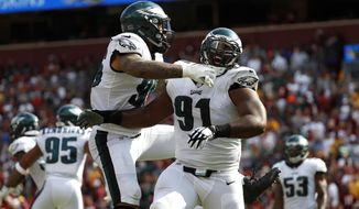 Philadelphia Eagles defensive tackle Fletcher Cox, right, celebrates with Derek Barnett after officials reviewed and confirmed a play in which Washington Redskins quarterback Kirk Cousins fumbled and Cox recovered and scored a touchdown in the second half of an NFL football game, Sunday, Sept. 10, 2017, in Landover, Md. Philadelphia won 30-17. (AP Photo/Alex Brandon)