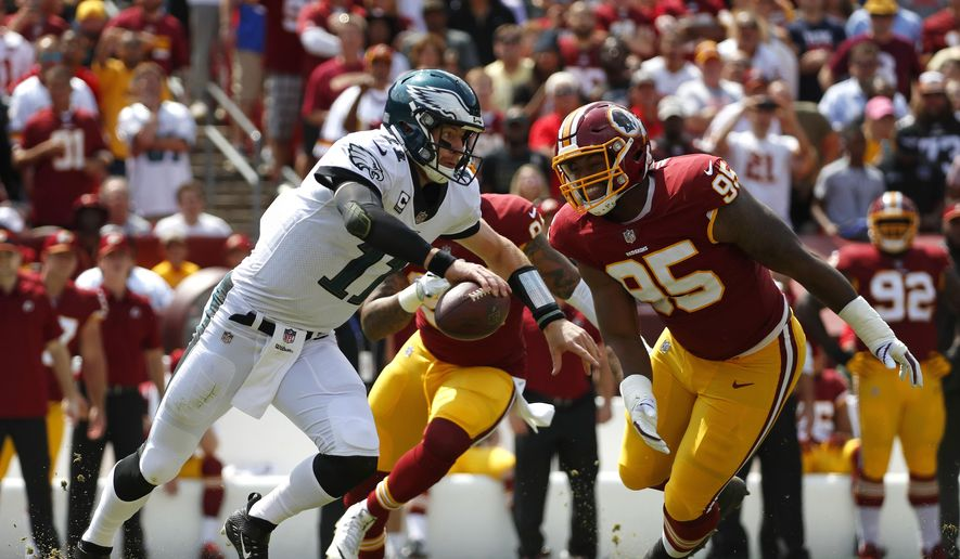 Philadelphia Eagles quarterback Carson Wentz, left, tries to outrun Washington Redskins defensive end Jonathan Allen (95) and outside linebacker Preston Smith as he looks for a receiver in the first half of an NFL football game, Sunday, Sept. 10, 2017, in Landover, Md. (AP Photo/Alex Brandon) **FILE**