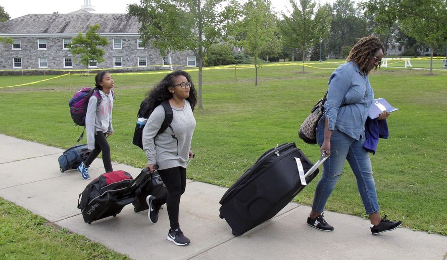 In this Aug. 31, 2017 photo, first generation college student Minori Kawano, of New York, center, arrives at Middlebury College accompanied by her mother, Mercy Kawano, right, and younger sister Mayomi Kawano, left, in Middlebury, Vt. The school is among a number of colleges and universities across the country with special programs to help ease the transition to college for students who are the first in their families to attend. (AP Photo/Wilson Ring)