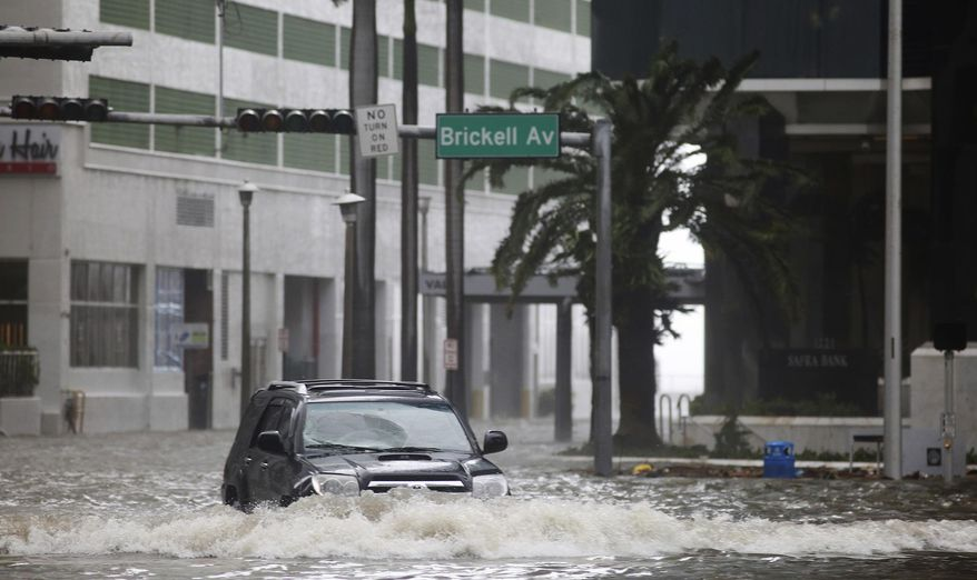 A vehicle drives on flooded Brickell Avenue in Miami on Sunday, Sept. 10, 2017, as Hurricane Irma passes. (Mike Stocker/South Florida Sun-Sentinel via AP)