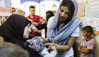 """Priyanka Chopra, a UNICEF Goodwill Ambassador, greets a Syrian woman and her baby at UNICEF's Makani Center in Amman, Jordan, Sunday, Sep. 10, 2017. Chopra said the world needs to do more to help those displaced by war -- through individual donations if governments won't step up. The Bollywood veteran who is increasingly making her mark in the U.S. also tells The Associated Press in an interview that she didn't realize until working in America that it's """"difficult for a woman of color"""" to be cast in a wide range of roles. (AP Photo/Lindsey Leger)"""