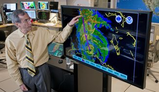 Ed Rappaport, the acting director of the National Hurricane Center, draws a line to illustrate the projected track of Hurricane Irma up Florida's west coast Saturday, Sept. 9, 2017 during a television interview. (AP Photo/Andy Newman)
