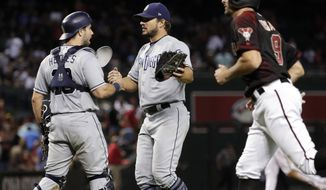 San Diego Padres catcher Austin Hedges, left, and San Diego Padres relief pitcher Brad Hand celebrate after a baseball game against the Arizona Diamondbacks, Saturday, Sept. 9, 2017, in Phoenix. The Padres won 8-7. (AP Photo/Matt York)