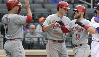 Cincinnati Reds' Tucker Barnhart, right, celebrates with Zach Vincej and Eugenio Suarez, left, after hitting a three-run home run during the ninth inning of a baseball game against the New York Mets, Sunday, Sept. 10, 2017, in New York. (AP Photo/Bill Kostroun)