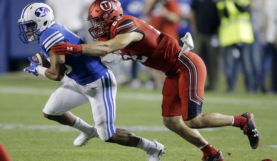 Utah defensive back Chase Hansen, right, tackles BYU wide receiver Aleva Hifo during the first half of an NCAA college football game Saturday, Sept. 9, 2017, in Provo, Utah. (AP Photo/Rick Bowmer)