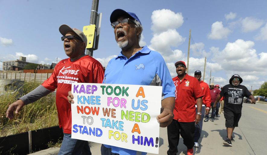 Protesters march in support of former quarterback Colin Kaepernick outside Ford Field and an NFL football game between the Detroit Lions and the Arizona Cardinals in Detroit, Sunday, Sept. 10, 2017. (AP Photo/Jose Juarez)