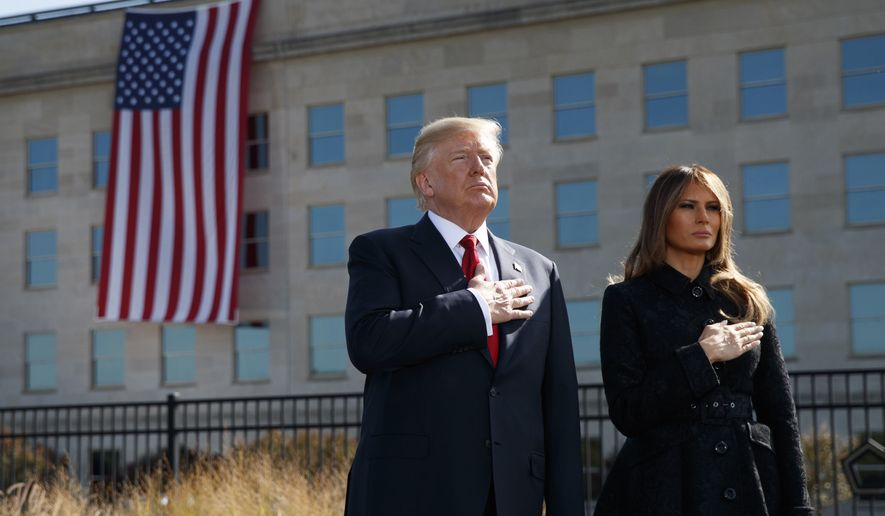 "President Donald Trump and first lady Melania Trump stand as ""Taps"" is played during a ceremony to mark the anniversary of the Sept. 11 terrorist attacks, Monday, Sept. 11, 2017, at the Pentagon. (AP Photo/Evan Vucci)"