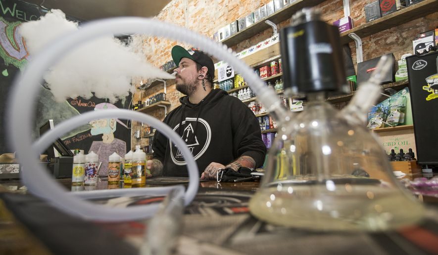 Myk Londino, manager of Vape O2, blows a plume of smoke at his shop in Philadelphia. An E Hookah is in the foreground. (Charles Fox/The Philadelphia Inquirer via AP)