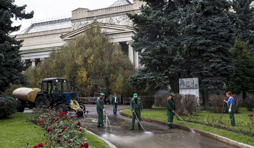 "Municipal workers wash a path way in front of the ""Autumn"" installation of China's artist Cai Guo-Qiang in the Moscow Pushkin State Art Museum in Moscow, Russia, Monday, Sept. 11, 2017. The ""October"" exhibition of Cai Guo-Qiang celebrates the 100th anniversary of the Russian Revolution. (AP Photo/Pavel Golovkin)"
