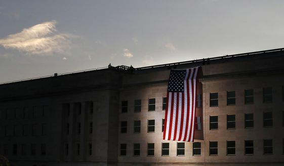 A U.S. flag is unfurled at sunrise at the Pentagon on the 16th anniversary of the Sept. 11, 2001, attacks, on Monday, Sept. 11, 2017. (AP Photo/Jacquelyn Martin)