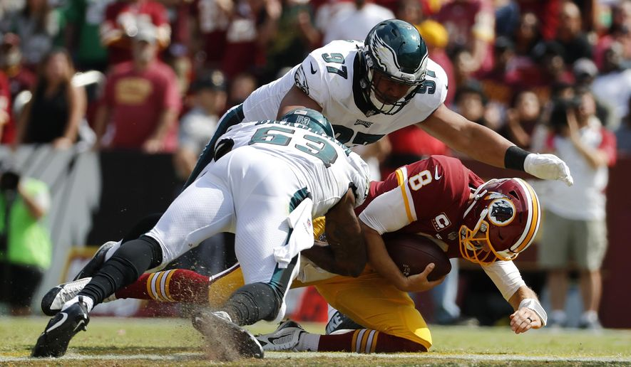 Washington Redskins quarterback Kirk Cousins, bottom right, slides as he is pressured by Philadelphia Eagles defensive tackle Destiny Vaeao, top, and outside linebacker Nigel Bradham in the second half of an NFL football game, Sunday, Sept. 10, 2017, in Landover, Md. (AP Photo/Alex Brandon)