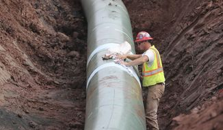 In an Aug. 21, 2017 photo, a pipe fitter lays the finish finishing touches to the replacement of Line 3 stretch before it is covered up. Enbridge already has started building the 14-mile stretch of Line 3 from the Minnesota line to its terminal in Superior, Wis. In filings with the Public Utilities Commission Monday, Sept. 11, The Minnesota Department of Commerce says Enbridge Energy has failed to establish the need for its proposal to replace its aging Line 3 crude oil pipeline across northern Minnesota. Instead, the department says it might be better to just shut down the existing line.  (Richard Tsong-Taatarii/Star Tribune via AP)