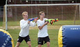 In this undated photo, Cinnaminson High School varsity soccer players Jake Weick, left, and Mike Lutz take part in a Nerf war at the school, in Cinnaminson, N.J. Austin Dasher, a 17-year-old Delanco teen, started his own company recently called Nerf Wars and does Nerf events all around the state and in New York as well.  (Camden Courier-Post via AP)