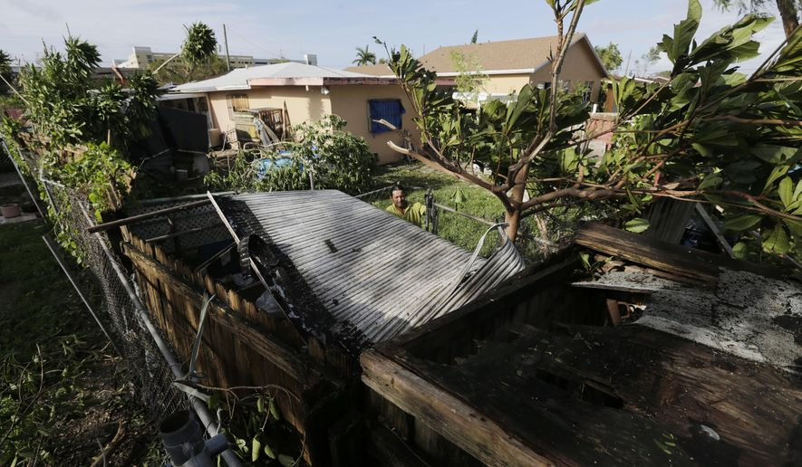 Bayardo Perez prepares to dismantle the mangled tin roof of his shed in Sweetwater, Fla., Monday, Sept. 11. Inland communities like Sweetwater were spared the storm surge from Hurricane Irma, but streets were swamped, fences and trees fell, cars got stuck in floodwater, and the ground will remain saturated as trillions of gallons of ocean water flow south through the Everglades. (AP Photo/Jason Dearen)