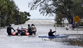 Rescue workers, left, search a neighborhood for flood victims as a man on a kayak down the street after Hurricane Irma brought floodwaters to Jacksonville, Fla. Monday, Sept. 11, 2017. (AP Photo/John Raoux)