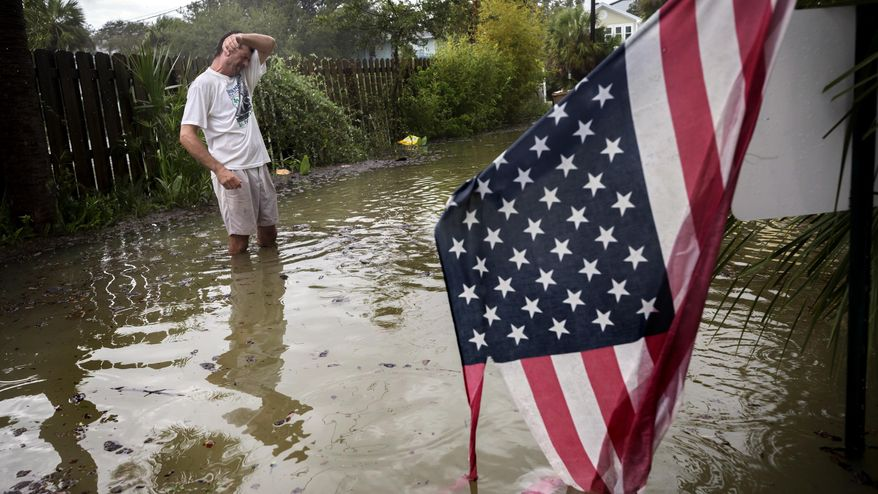 Tybee Island resident Joe Murphy wipes the sweat off his face while standing in knee deep water from Tropical Storm Irma outside his house, Monday, Sept., 11, 2017, on Tybee Island, Ga. (AP Photo/Stephen B. Morton)