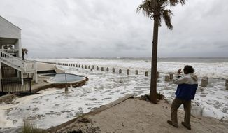 Pete Peters, from Mt. Pleasant, S.C., takes photos of the pounding surf at high tide caused by Hurricane Irma in the Wild Dunes Resort community of the Isle of Palms, S.C., Sunday, Sept. 10, 2017. (AP Photo/Mic Smith)