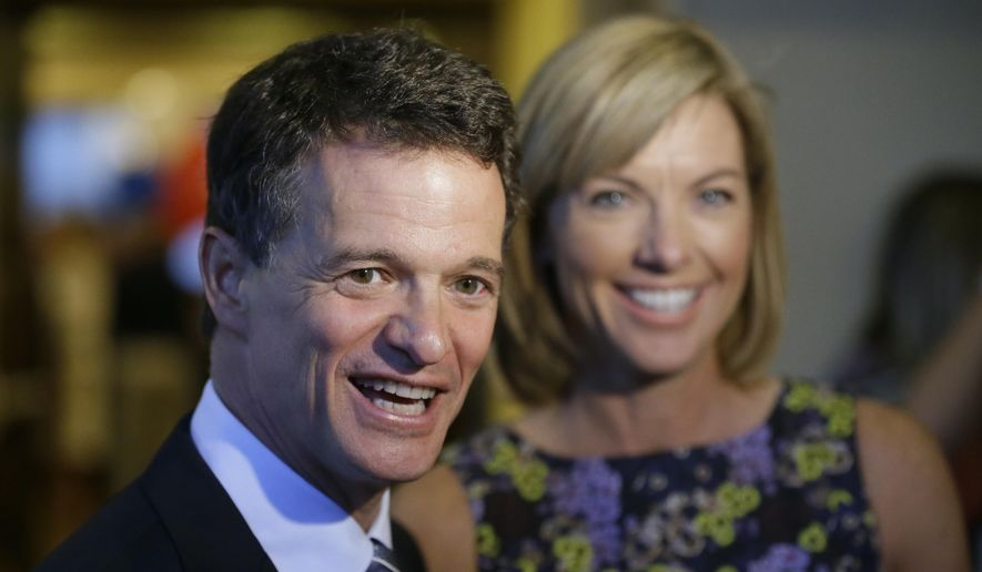 FILE - In this Aug. 5, 2014 file photo, Republican David Trott, a candidate for Michigan's 11th congressional district, stands next to his wife, Kappy, during an interview at his election night party in Troy, Mich. In a statement Monday, Sept. 11, 2017, Trott, R-Mich., says he will not seek re-election. (AP Photo/Carlos Osorio, File)