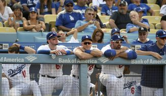 Los Angeles Dodgers' Alex Verdugo (61), Chase Utley (26), Adrian Gonzalez and Alex Wood, from left, look on from the dugout during the ninth inning of their 8-1 loss to the Colorado Rockies during a baseball game, Sunday, Sept. 10, 2017, in Los Angeles. (AP Photo/Michael Owen Baker)
