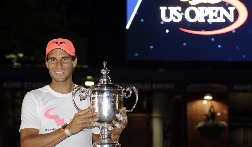 Rafael Nadal, of Spain, poses for photographers after with the championship trophy after beating Kevin Anderson, of South Africa, in the men's singles final of the U.S. Open tennis tournament, Sunday, Sept. 10, 2017, in New York. (AP Photo/Julio Cortez)