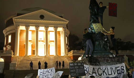Black Lives Matter protesters cover a statue of Thomas Jefferson with a tarp during a rally in front of the Rotunda at the University of Virginia on Tuesday. (Photo by Zack Wajsgras/The [Charlottesville, Va.] Daily Progress)