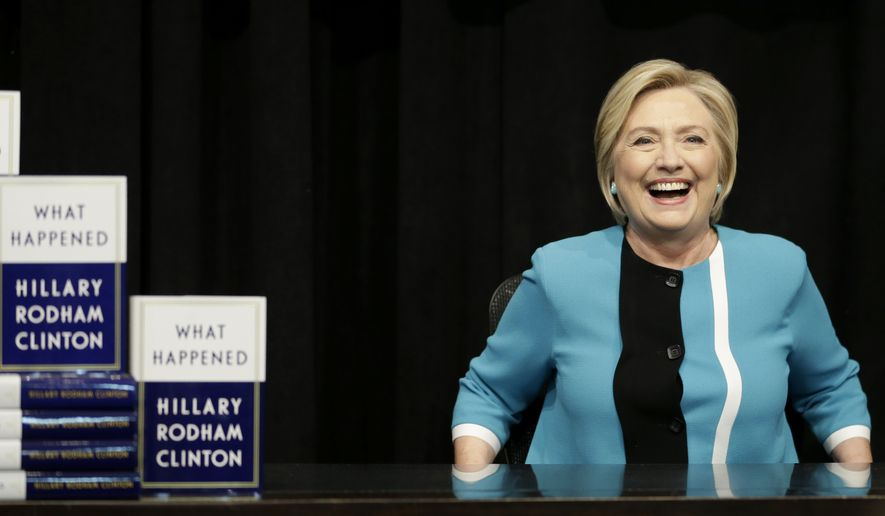 "Hillary Rodham Clinton prepares to sign copies of her book ""What Happened"" at a book store in New York, Tuesday, Sept. 12, 2017. (AP Photo/Seth Wenig)"