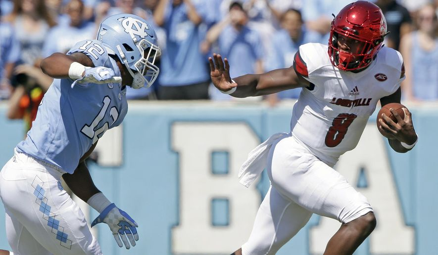 FILE - In this Sept. 9, 2017, file photo, Louisville quarterback Lamar Jackson (8) runs the ball as North Carolina's Tomon Fox (12) chases him during the first half of an NCAA college football game, in Chapel Hill, N.C. Jackson, the Heisman Trophy winner and All-American, leads the nation in total offense at 505 yards per game heading into a showdown with No. 3 Clemson. (AP Photo/Gerry Broome, File)