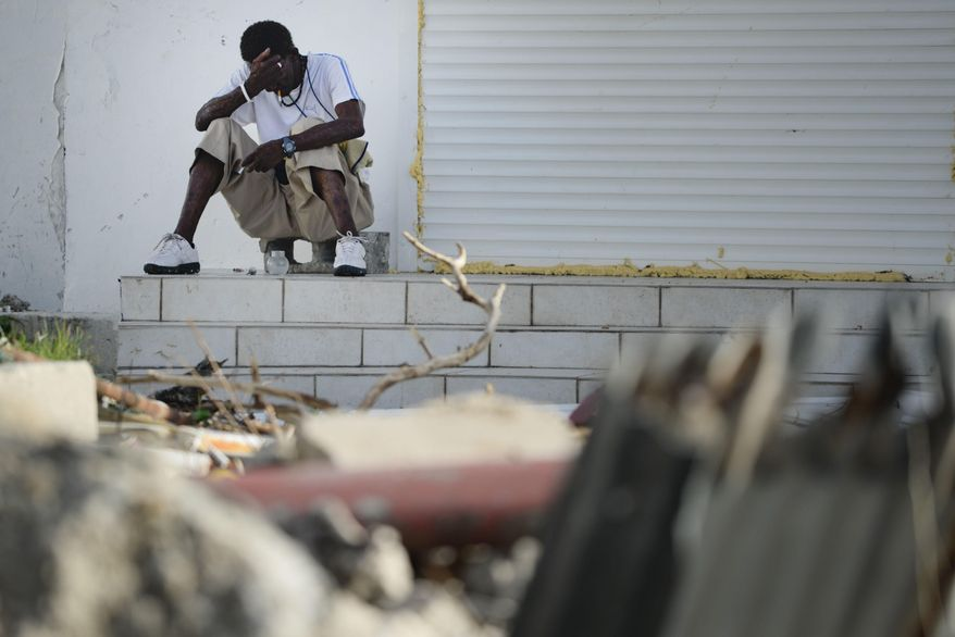 A sits on a porch on the destroyed Philipsburg after the passing of Hurricane Irma in St. Martin, Monday, Sept. 11, 2017. Irma cut a path of devastation across the northern Caribbean, leaving thousands homeless after destroying buildings and uprooting trees. (AP Photo/Carlos Giusti)