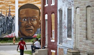 A mural depicting Freddie Gray is seen past blighted row homes in Baltimore, at the intersection where Gray was arrested. The U.S. Department of Justice won't bring federal charges against six police officers involved in the arrest and death of Freddie Gray, a young black man whose death touched off weeks of protests and unrest in Baltimore. The officers were charged by state prosecutors after Gray's neck was broken in the back of a police transport wagon in April of 2015. (AP Photo/Patrick Semansky File)