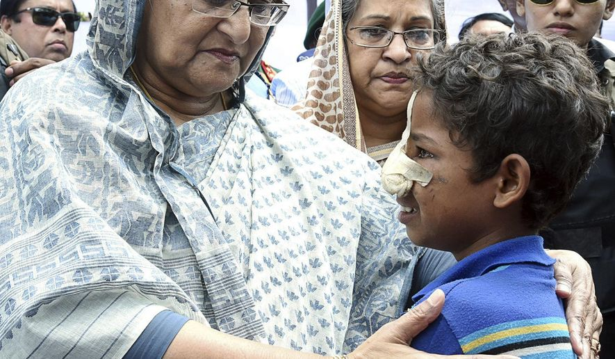 Bangladeshi Prime Minister Sheikh Hasina, center, meets with a Rohingya Muslim child at Kutupalong refugee camp, near the border town of Ukhia, Bangladesh, Tuesday, Sept. 12, 2017. Hasina visited the struggling refugee camp that has absorbed some of the hundreds of thousands of Rohingya who fled recent violence in Myanmar, a crisis she said left her speechless. (AP Photo/Saiful Kallol)