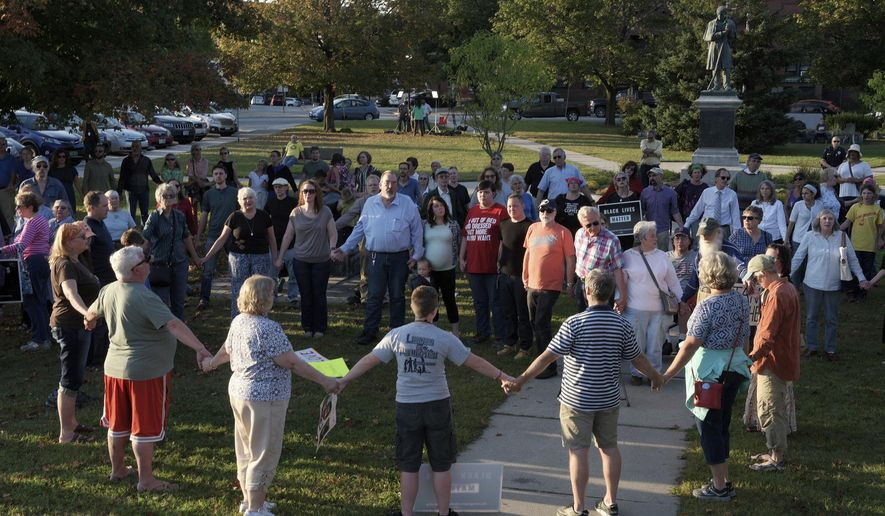 "A chorus of ""We Shall Overcome"" rises from a gathering against racism in Broad Street Park in Claremont, N.H., Tuesday, Sept. 12, 2017. The demonstration was inspired by violence last month against an 8-year-old biracial boy that occurred while he played with a group of teenagers outside his home. (James M. Patterson/The Valley News via AP)"
