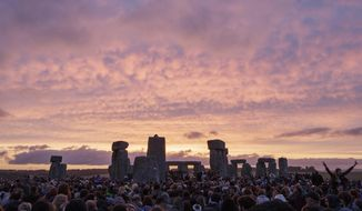 FILE - In this Sunday, June 21, 2015 file photo, the sun rises as thousands of revellers gather at the ancient stone circle Stonehenge to celebrate the Summer Solstice, the longest day of the year, near Salisbury, England. British authorities have approved a contentious road tunnel under Stonehenge _ but have altered its route so it doesn't impede views of the sun during the winter solstice, it was reported on Tuesday, Sept. 12, 2017. (AP Photo/Tim Ireland, File)