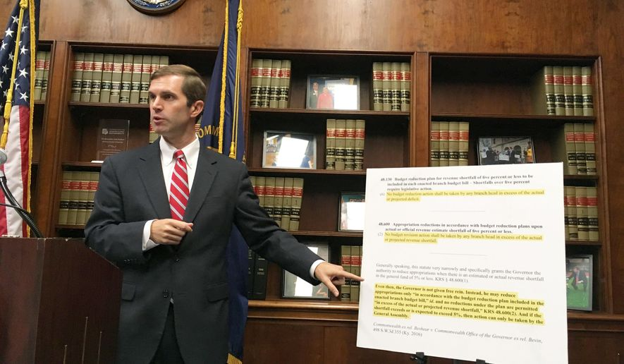 Kentucky Democratic Attorney General Andy Beshear points to state law he says prohibits the governor from implementing spending cuts that exceed a projected shortfall, in Frankfort, Ky., on Tuesday, Sept. 12, 2017.  (AP Photo/Adam Beam)