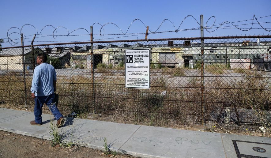 FILE--This July 29, 2016, file photo shows a pedestrian walking past the outside of an old derelict factory where the Slauson-Wall Park is meant to be built in Los Angeles. Lawmakers want to spend $700 million to build new parks as part of a $4 billion bond proposal, but many parks promised under the last bond in 2006 still aren't finished. (AP Photo/Nick Ut, file)