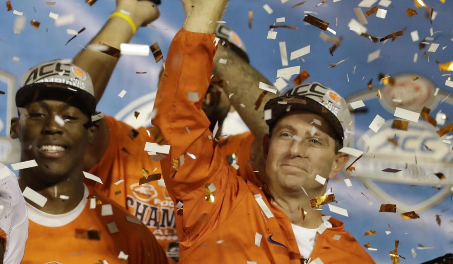 FILE - In this Dec. 4, 2016, file photo, Clemson head coach Dabo Swinney raises the Atlantic Coast Conference championship NCAA college football trophy after defeating Virginia tech 42-35, in Orlando, Fla.  If No. 3 Clemson wants its third straight Atlantic Coast Conference title,it's offense will have to find its rhythm quickly. (AP Photo/Chris O' Meara)