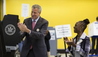New York Mayor Bill de Blasio and his wife Chirlane McCray applaud after they both voted in the Democratic primary, Tuesday, Sept. 12, 2017, in the Brooklyn borough of New York. The mayor faces a crowded primary field, but no challengers with his organizing power or financial muscle, as he seeks a second term as the leader of the country's largest city. (AP Photo/Mark Lennihan)