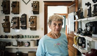 In this Aug. 24, 2017 photo, Kay Demrow stands in the Footville Telephone Museum among historical telephones from many decades in Footville, Wis. (Angelea Major/The Janesville Gazette via AP)