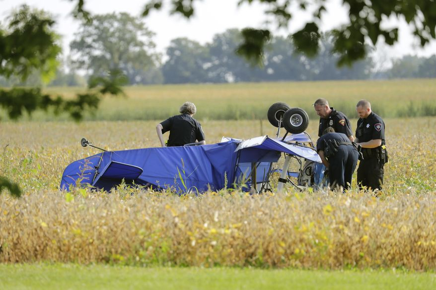 Winnebago County Sheriff's Office officials investigate a plane crash in a field along Winnebago County G near State 76 Tuesday, Sept. 12, 2017, in the Town of Vinland, Wis. According to Capt. Lara Vendola-Messer of the sheriff's department, the sole occupant in the plane, a man, died. (Dan Powers/The Post-Crescent via AP)