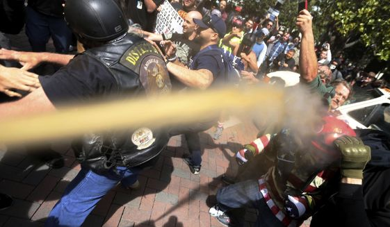 FILE - In this April 15, 2017 file photo, pepper spray is used as anti and pro-Donald Trump protesters clash during competing demonstrations at Martin Luther King Jr. Civic Center Park in Berkeley, Calif. Police in Berkeley, California say they need an additional weapon to combat violent protests that have repeatedly hit the city. The city council will decide Tuesday, Sept. 12, whether to let officers use pepper spray to control crowds that turn violent. (Anda Chu/San Jose Mercury News via AP, File)