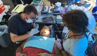 In this Friday, July 21, 2017, photo, dental student Carl Leiner, left, checks Lisa Kantsos teeth at the Remote Area Medical clinic in Wise, Va. Kantsos and hundreds of other uninsured patients came to the rural clinic for free dental and medical care. (AP Photo/Dylan Lovan)