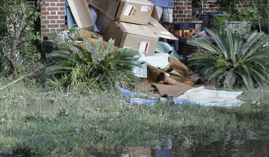 A home owner removes water logged items from his home as floodwaters fill the street in the San Marco area of Jacksonville, Fla. in the aftermath of Hurricane Irma, Tuesday, Sept. 12, 2017. (AP Photo/John Raoux)