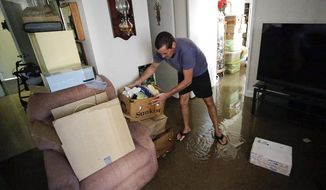 Joseph Dupuis III stacks items off the floor in his parents water logged apartment on the St. John's River in Jacksonville, Fla. in the aftermath of Hurricane Irma, Tuesday, Sept. 12, 2017. (AP Photo/John Raoux)