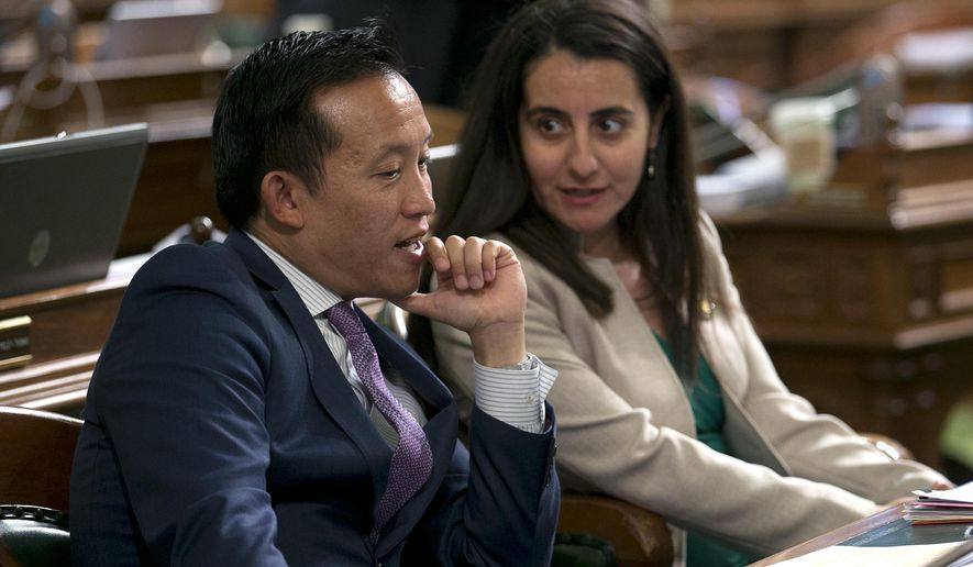 Assemblyman David Chiu, D-San Francisco talks with his seat mate, Assemblywoman Monique Limon, D-Goleta, after the Assembly approved Chiu's immigration bill, Monday, Sept. 11, 2017, in Sacramento, Calif. By a 49-18 vote the Assembly approved AB291 that prohibits landlords from disclosing the immigration status of tenants or threatening to report tenants to immigration authorities. (AP Photo/Rich Pedroncelli)